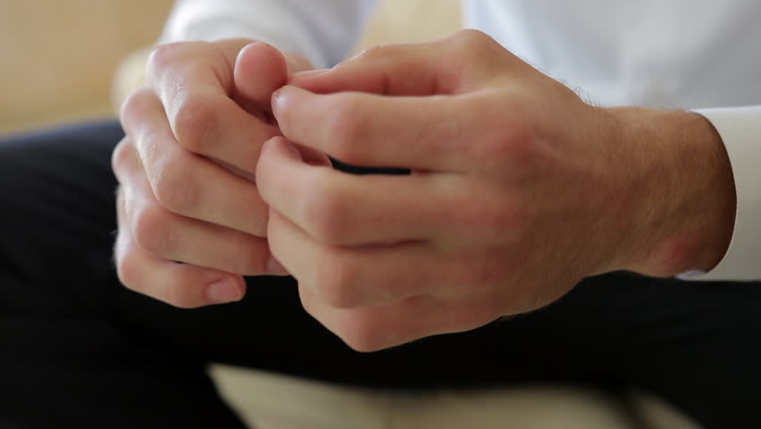 Close up of male hands clenched together in the air, then rubbed, and touching fingers and palms with fingers, concentrating , thinking or making decision, nervous. Male dressed classic fo business or