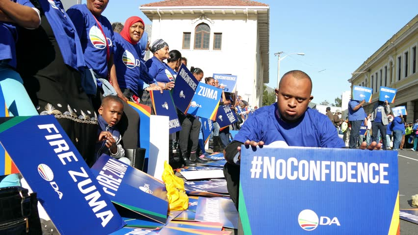 """CAPE TOWN SOUTH AFRICA, 8 AUGUST 2017, day of Zuma no confidence vote in parliament, DA group, low angle view of man sitting on street with """"no confidence"""" placard, women standing all dressed in blue"""