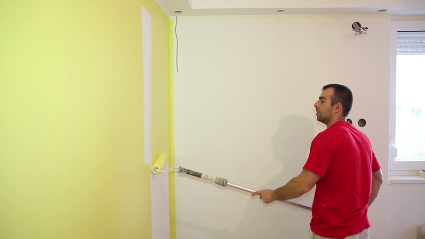 decorator using a long roller to paint a wall in yellow hd1080p - Decorator