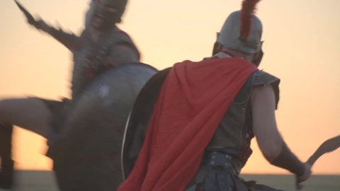 The tired gladiator attacks the other and he dodges and strikes back, slow motion