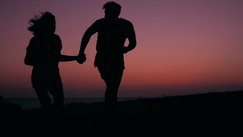 Silhouette of Young Teenage Couple in Love Running and Spinning at Beautiful Pink Sunset. HD Slowmotion Carefree Lifestyle Footage.