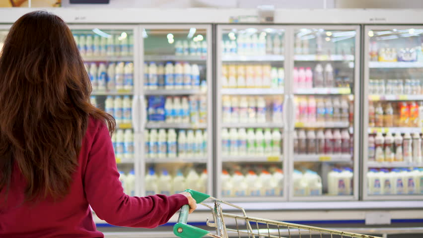 Advertise, Business, Food, Health Concept -  Woman in a supermarket standing in front of the freezer and choose buying fresh milk bottle. Drink milk for healthy.