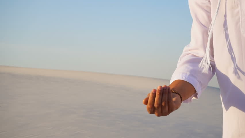 Close-up of face and hands of young Arab guy who takes sand in hand and lifts it to smiling face and blows through fingers fine white grains of sand in bottomless desert on hot summer day. Swarthy