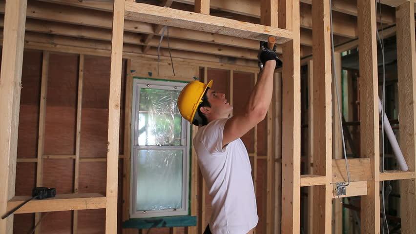 Builder hammering door frame in house construction site