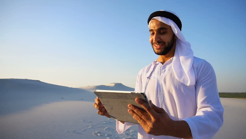 Portrait of stately Arabian Sheikh man who with smile on face holds tablet in hands. guy looks around desert and keeps record in gadget or writes down impressions of journey, standing in desert in