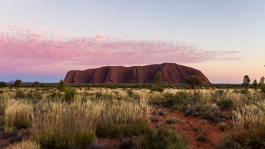 Uluru / Ayers Rock at sunrise with some clouds, Australia (timelapse)