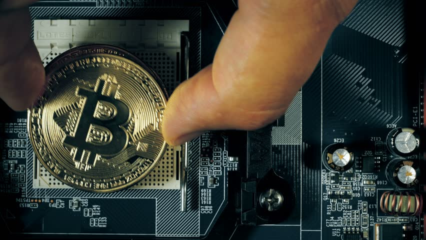 The man's hand puts the bitcoins in a column. Hand counting bitcoins on the motherboard. Crypto currency Gold Bitcoin - BTC - Bit Coin. Blockchain technology.
