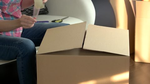 Woman packing box. Cardboard box with adhesive tape. Average moving cost.