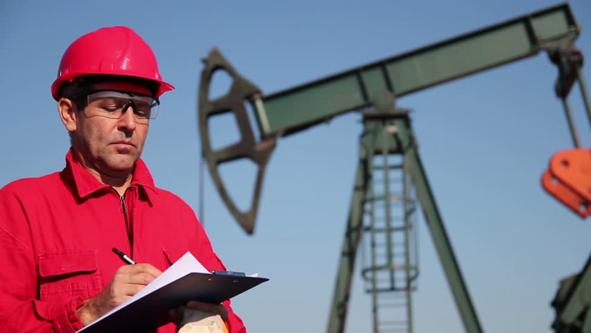 Oil Worker and Clipboard. Oil worker writing on clipboard next to pump jack. HD1080p.