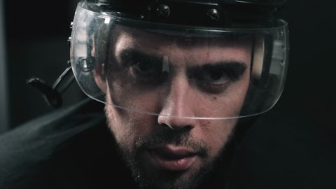Hockey player portrait close up with helmet, professional forward defender in dressing room before game, canadian hockey agressive power portrait