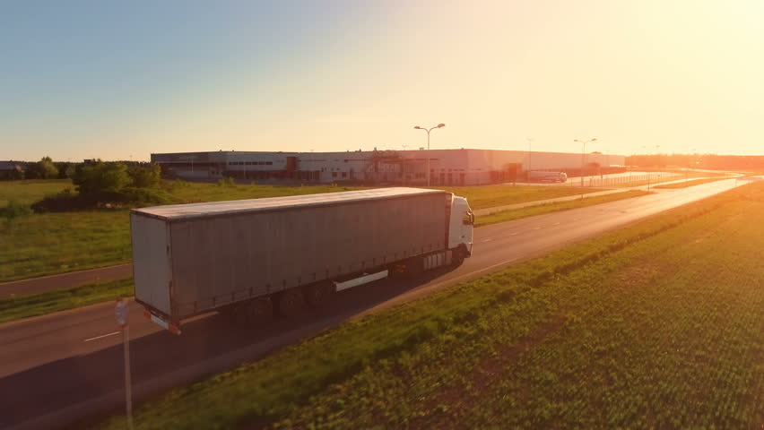 Aerial View of White Semi Truck with Cargo Trailer Moving on the Highway. In the Background Warehouses and Industrial Loading Buildings are Seen. Sunset. Shot on Phantom 4K UHD Camera.