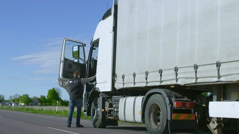 Truck Driver Crosses the Road in the Rural Area and Gets into His White Semi Truck with Cargo Trailer Attached. Sun Shines and Highway is Empty. Shot on RED EPIC-W 8K Helium Cinema Camera.