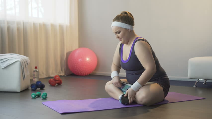 Obese girl hardly trying to take lotus position for finding peace of mind, yoga | Shutterstock HD Video #29803228