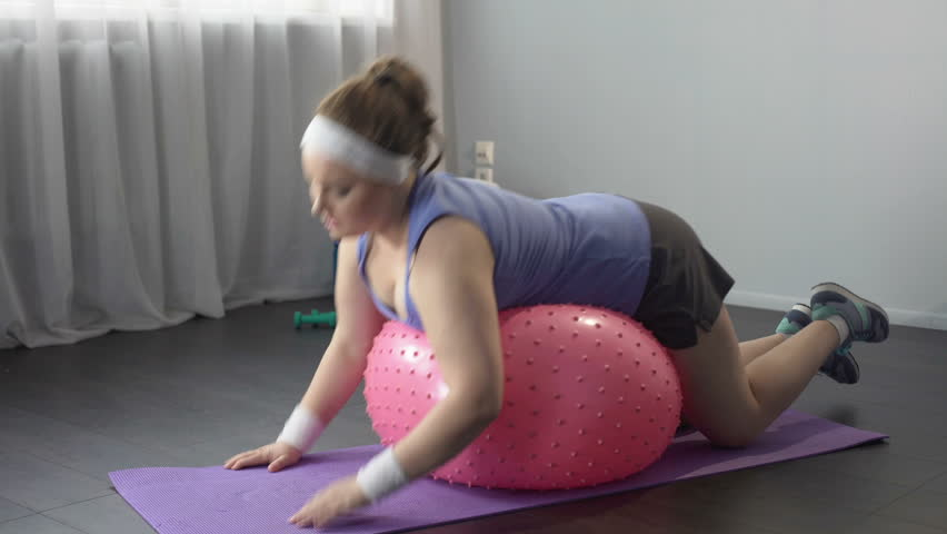 Funny lazy girl lying on big fitness ball, unable to do weight loss exercises | Shutterstock HD Video #29803528