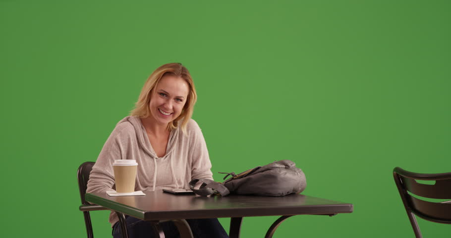 Cute woman leaves a cafe on green screen. On green screen to be keyed or composited.