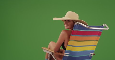 Happy woman sitting on a lounge chair on green screen. On green screen to be keyed or composited.