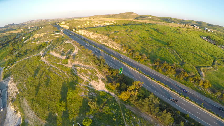 Quadrocopter flying along highway, filming fascinating landscapes of Cyprus