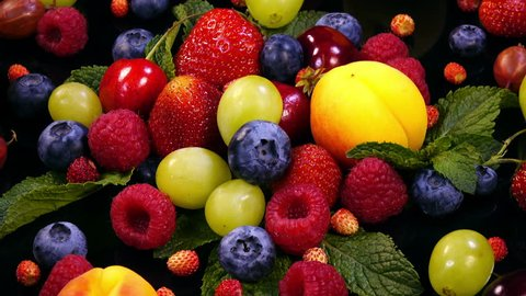 Background with mixed fresh juicy berries and fruits and mint leaves on black background in 4K. Closeup view rotation.
