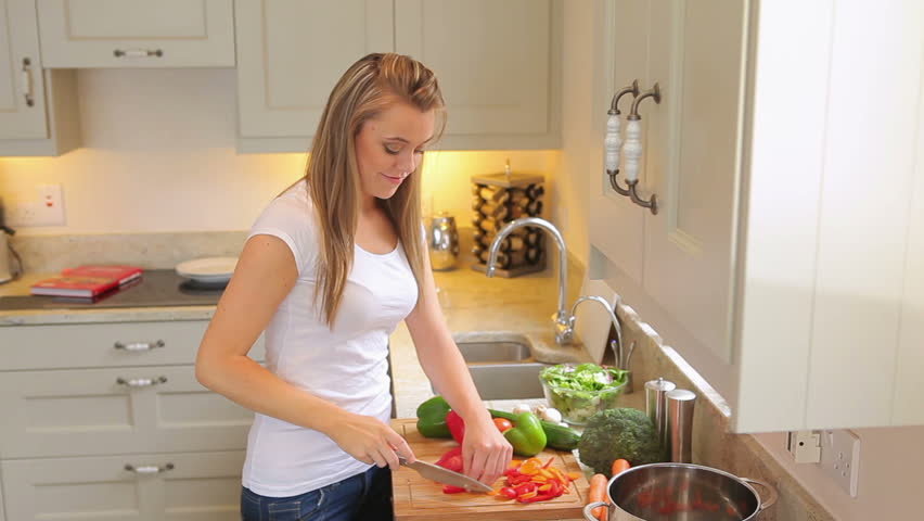 Woman Standing In The Kitchen Cutting Vegetables Putting In A Pot ...