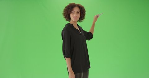 A young black female teacher explains math on green screen. On green screen to be keyed or composited.