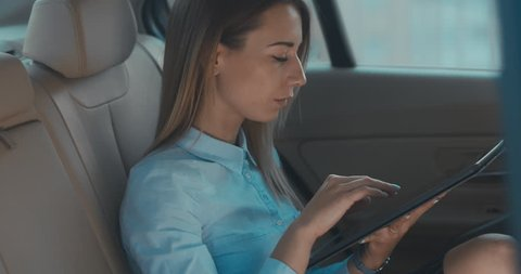 Attractive elegant business lady executive rides in a car with brown leather seats, using her portable tablet computer. 4K UHD RAW edited footage