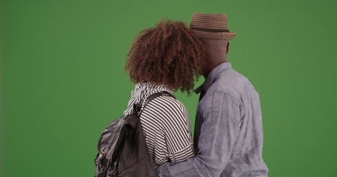 Black man and woman embrace each other while staring off on green screen. On green screen to be keyed or composited.