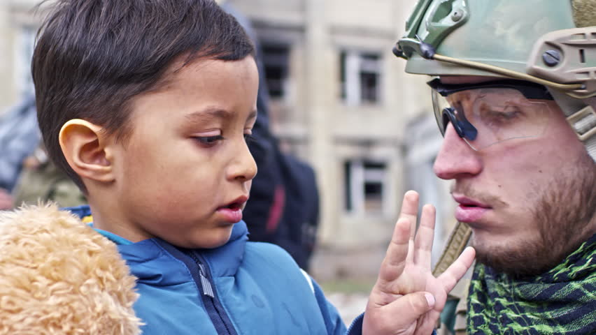 Close up of Caucasian soldier in helmet and safety glasses chatting with little Syrian refugee boy with dirty face holding plush toy