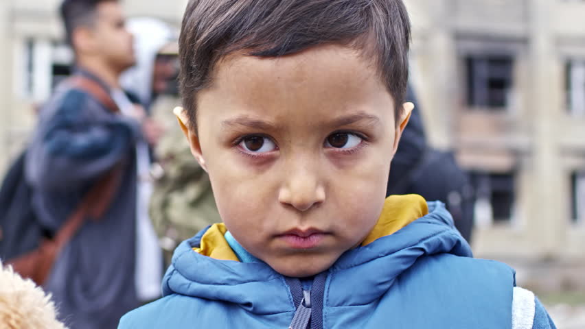 Tilt up with close up of little Syrian refugee boy with plush toy wearing dirty puffy vest and looking at camera with sadness