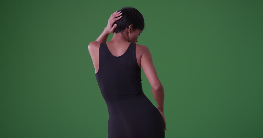 Young black woman dancing sensually and looking at the camera on green screen. On green screen to be keyed or composited.