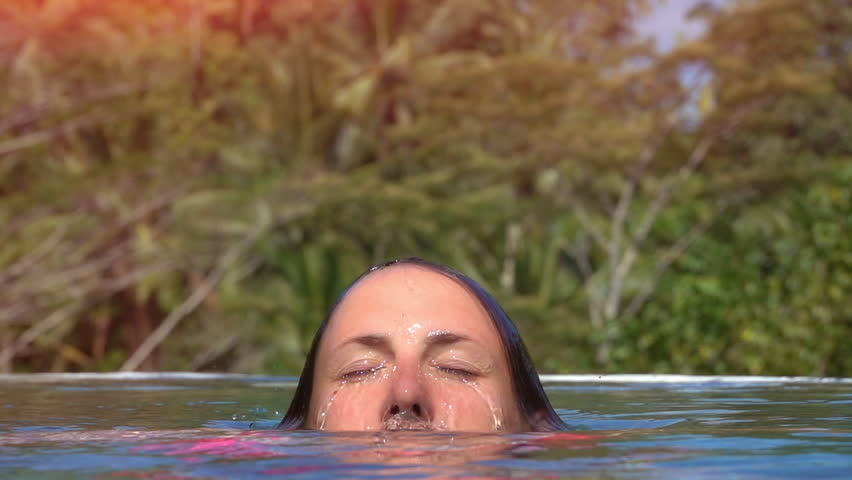 SLOW MOTION, CLOSE UP, LENS FLARE: Young girl relaxing on summer vacation, in infinity pool in sunny Bali. Woman comes up for air to water surface. Female holding breath and swimming underwater
