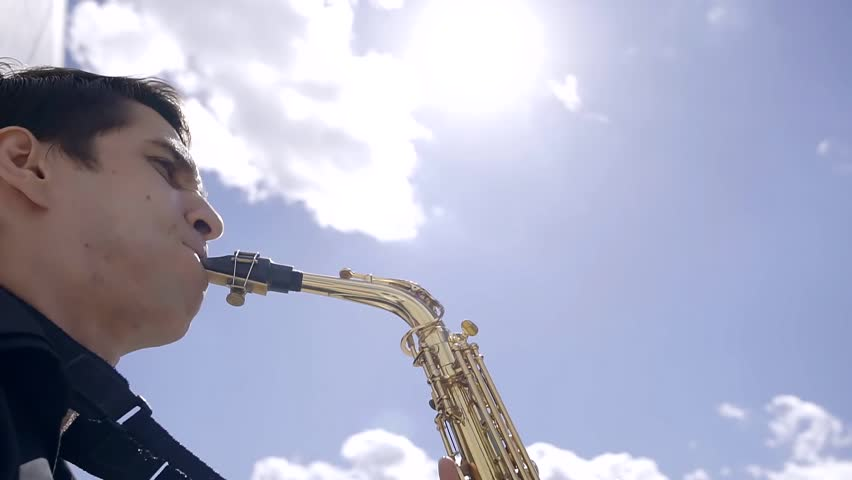 young musician saxophonist plays jazz on his instrument in a Sunny summer day on a city street
