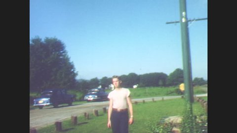 1940s: Young man walks across grass. Field, train tracks, and road in country. Cars drive on road. Mountains and field.