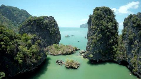 Phang Nga Bay of Thailand. Tourists kayaking among limestone cliffs.
