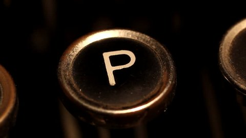 "A male finger presses the letter ""P"" key on an old typewriter."