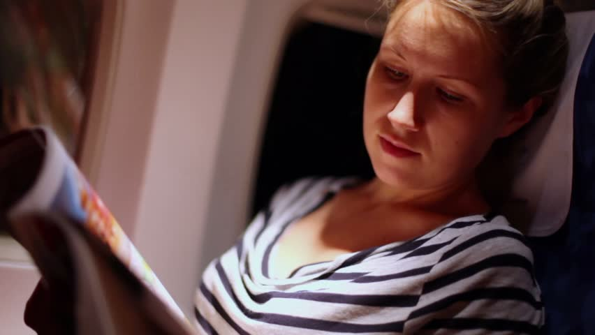 Young woman sits in chair near illuminator of airplane and reads magazine