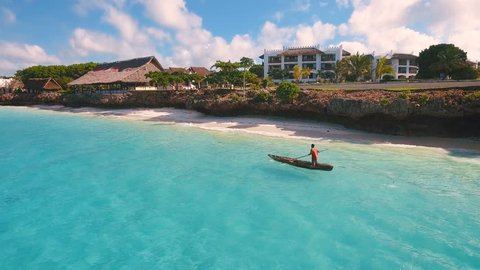 Aerial view of a poor fisherman with a torn shirt sails on a small boat on clear blue water along a tropical beach with beautiful hotels in Africa. Indian Ocean. Zanzibar. 2017