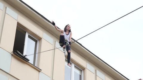 OLESNICA near WROCLAW, POLAND - AUG 12, 2017: Free open air street circus busker festival. Trick Walking On A Tightrope A Girl Acrobat Breaks Falls Down