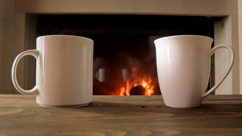 Closeup slow motion footage of two cups of tea standing on wooden table next to burning fireplace | Shutterstock HD Video #29939488