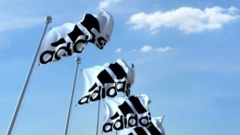 Waving flags with Adidas logo against sky, seamless loop. 4K editorial animation