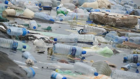 Environmental pollution. Plastic bottles, bags, trash in river, lake. Rubbish and pollution floating in water. Slow motion