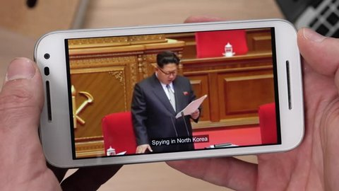 Watching a video of Kim Jong Un giving a speech on a smartphone.