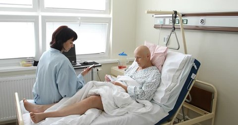 middle age woman patient with cancer in hospital on oncology department visited by her girlfriend. She hope in healing.