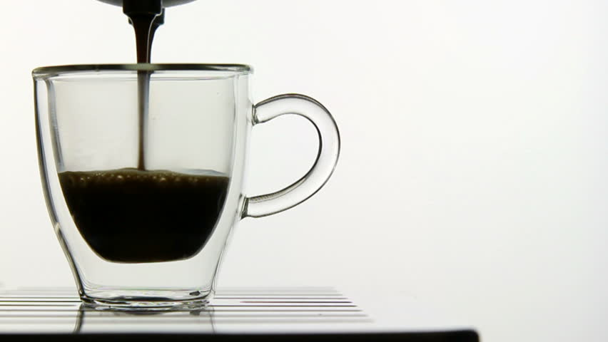 making espresso in glass transparent double-sided coffee cup, studio isolated shot, slow motion