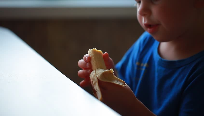 Video boy is eating a banana sitting at the table | Shutterstock HD Video #29983678
