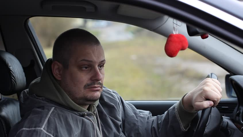 Depressed man drinking alcohol in car