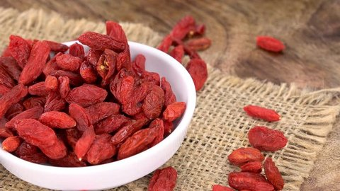 Goji Berries rotating on a wooden plate as seamless loopable 4K UHD footage