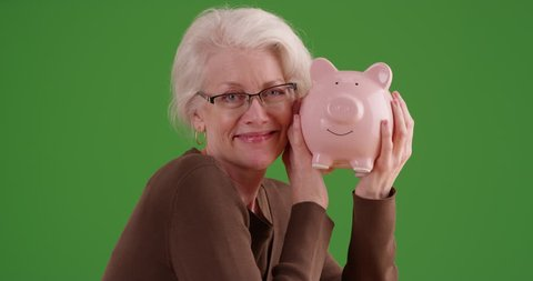Cheerful senior woman shaking piggy bank smiling at camera on greenscreen. Portrait of mature woman saving money holding up piggy bank on green screen to be keyed or composited.