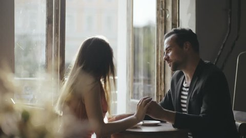Couple lovers sitting at a table cafe. Handsome man touching hand of his beloved woman at table. Young couple man and woman talking at a table trendy cafe. First date lovers