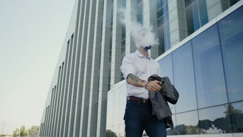 Confident well-dressed man with beard vaping an electronic cigarette