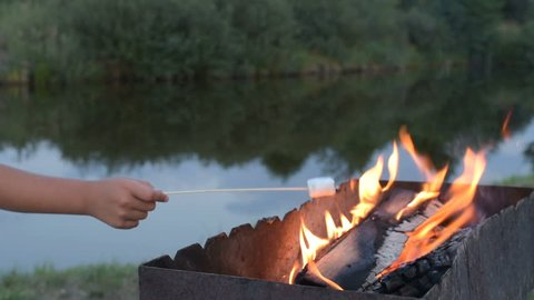 Marshmallows on camping fire. camping, travel, tourism, hike and people concept - happy family roasting marshmallow over campfire. marshmallow on skewers. marshmallows on stick over the bonfire